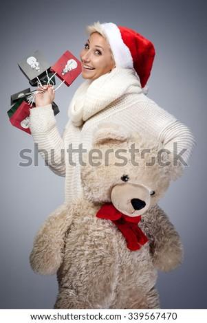 Smiling beautiful adult woman holding big teddy bear. Looking at camera. Studio shot. Winter style. - stock photo