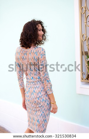 smiling beautiful adult woman with handbag on ancient street of little town. copy space - stock photo
