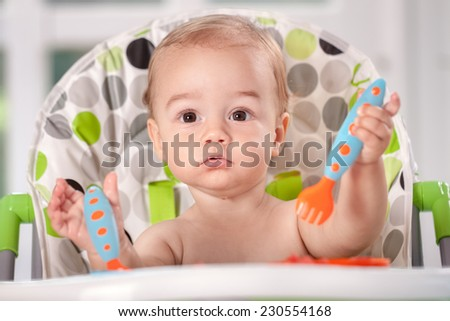 Smiling beautiful baby child holding cutlery - stock photo