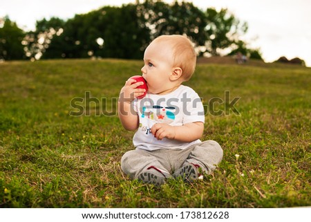 Smiling beautiful baby looking at camera and eating apple outdoors in sunlight