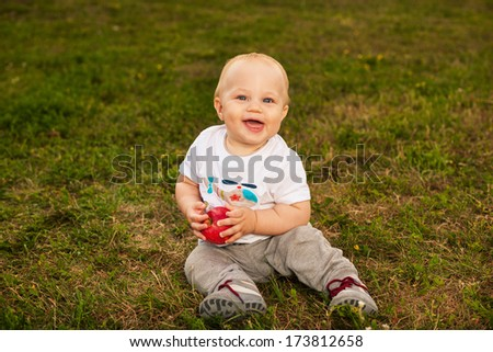 Smiling beautiful baby looking at camera and eating apple outdoors in sunlight - stock photo
