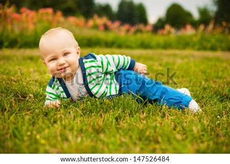 Smiling beautiful baby looking at camera outdoors in sunlight - stock photo