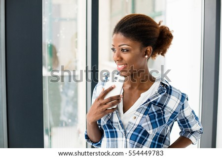 smiling beautiful black woman standing next to a window in checkered shirt at home and using her cellphone