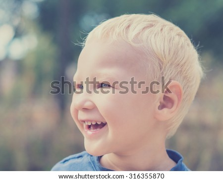 smiling beautiful blond boy. portrait. toned image