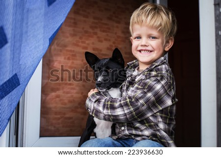 Smiling beautiful blond kid and his dog. Boy and Basenji. Outdoor portrait - stock photo