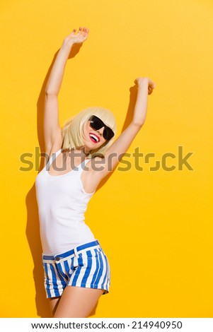 Smiling beautiful blonde young woman in a black sunglasses leaning on the wall with arms raised. Three quarter length studio shot on yellow background. - stock photo