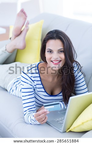 Smiling beautiful brunette doing online shopping on the couch in the living room - stock photo