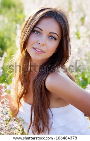 smiling beautiful brunette in the flowers  field - stock photo