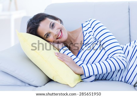 Smiling beautiful brunette relaxing on the couch and looking at camera in the living room - stock photo