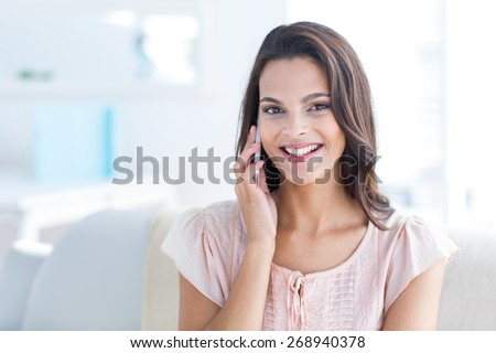 Smiling beautiful brunette relaxing on the couch and speaking on the phone in the living room - stock photo