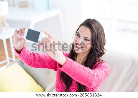 Smiling beautiful brunette relaxing on the couch and taking selfie in the living room - stock photo