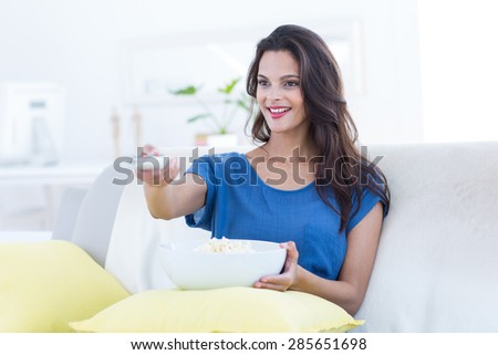 Smiling beautiful brunette relaxing on the couch with bowl of popcorn and changing tv station in the living room