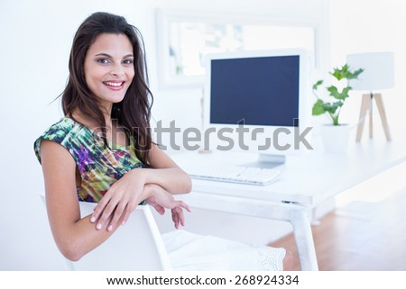 Smiling beautiful brunette sitting in front of her computer at her desk - stock photo