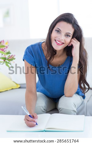 Smiling beautiful brunette writing in diary in the living room - stock photo