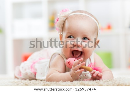 Smiling beautiful child girl lies with toy on carpet in nursery room - stock photo