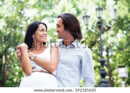 Smiling beautiful couple flirting outdoors in park - stock photo