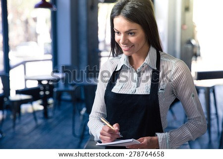 Smiling beautiful female waiter in apron with notepad and pen in cafe. Looking at camera - stock photo