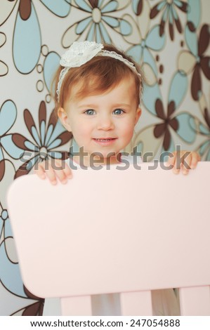 smiling beautiful girl behind chair - stock photo