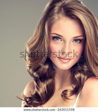 Smiling Beautiful girl brown hair with an elegant hairstyle , hair wave ,curly - stock photo