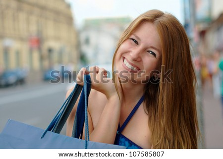 Smiling beautiful girl doing shopping at the street
