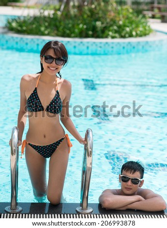 Smiling beautiful girl going upstairs from the pool while her boyfriend resting in the water - stock photo
