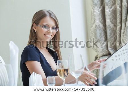Smiling beautiful girl in glasses posing with menu - stock photo