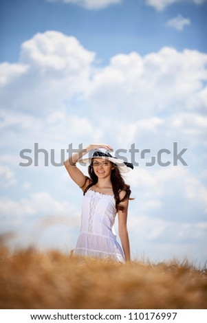Smiling Beautiful girl in white dress in wheat field