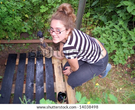 Smiling beautiful girl is painting wooden trellis - stock photo