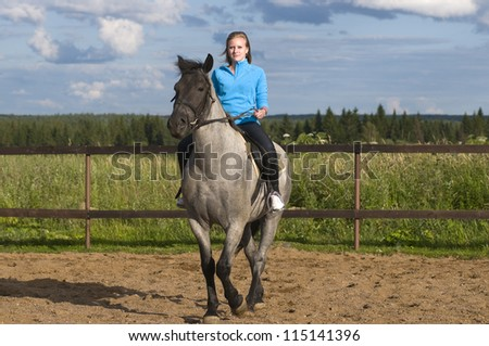 Smiling beautiful girl on a horse