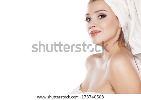 smiling beautiful girl with a towel on her head posing on white background