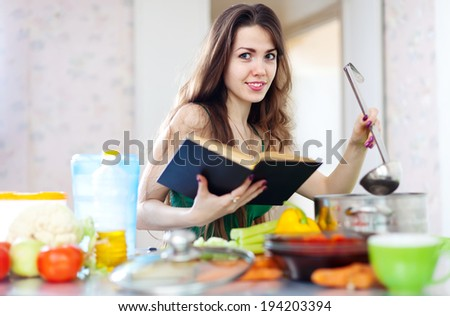 Smiling beautiful housewife cooking with ladle and cookbook in her kitchen  at home - stock photo