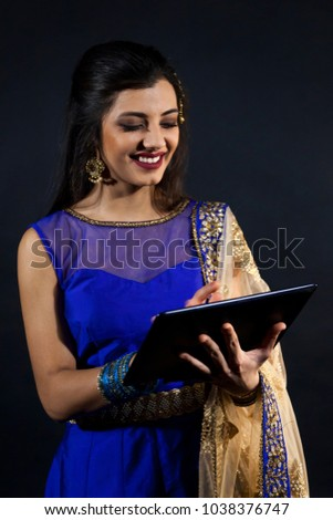 smiling beautiful indian girl consulting his laptop. young female model wears jewelry sets and traditional blue clothes