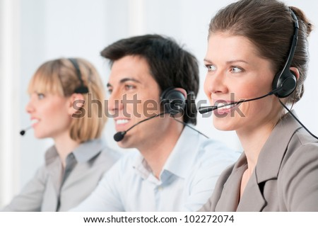 Smiling beautiful lady working at call center with colleagues in office - stock photo