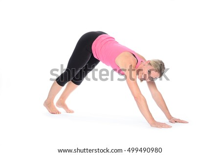 Smiling beautiful limber woman in yoga pose on hands and feet over isolated white background
