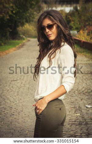 smiling beautiful long hair young woman portrait wearing white shirt and sunglasses outdoor shot sunny autumn day - stock photo