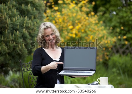 smiling beautiful mature blond woman pointing at laptop
