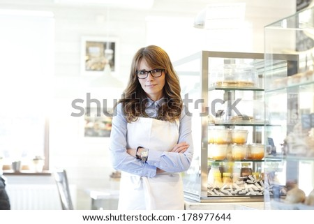 Smiling, beautiful mature woman. Small business bakery shop owner standing in her store. - stock photo