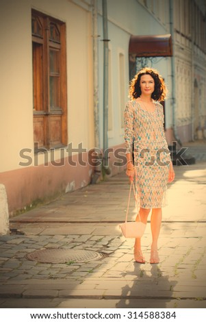 smiling beautiful middle-aged woman with a small handbag on the ancient street. instagram image filter retro style - stock photo