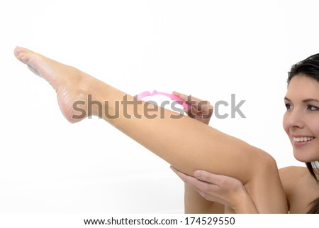 Smiling beautiful naked young woman shaving the hair on her legs with a pink disposable razor in the bath in a personal hygiene, spa and beauty concept - stock photo