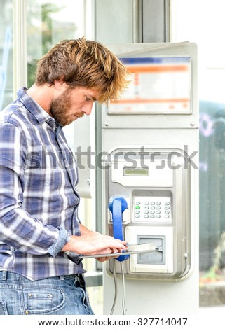 smiling beautiful senior man in obsolete phone box using tablet