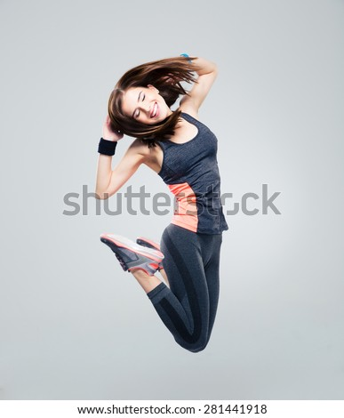 Smiling beautiful sports woman jumping over gray background - stock photo