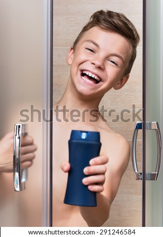 Smiling beautiful teen boy takes a shower in the bathroom - stock photo