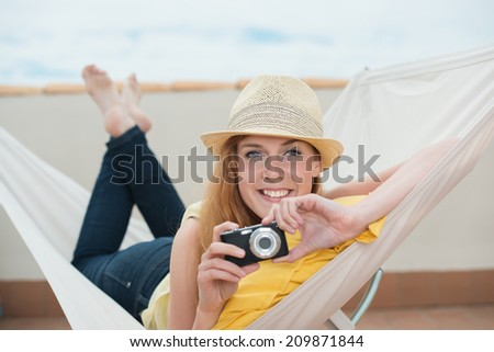 Smiling beautiful trendy young woman lying in a hammock on summer vacation holding a digital camera in her hand