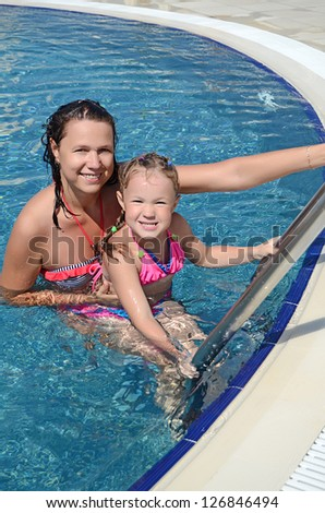 Smiling beautiful woman and her little cute daughter have a fun in pool outdoor - stock photo