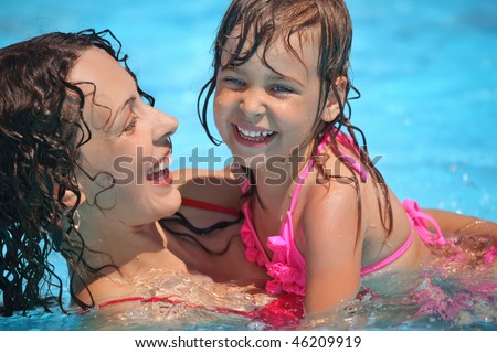 Smiling beautiful woman and little girl bathes in pool - stock photo