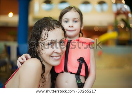 Smiling beautiful woman and little girl  in life-jacket after swimming in covered pool - stock photo