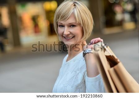 Smiling beautiful woman carrying shopping bags - stock photo