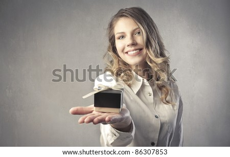 Smiling beautiful woman holding a small gift