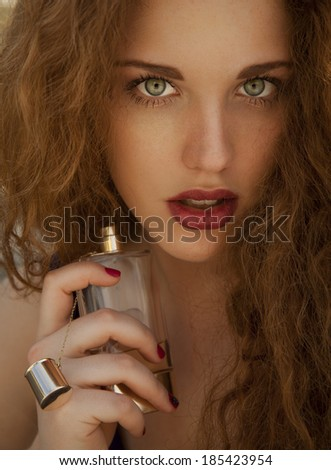Smiling beautiful woman holding bottle of perfume and smelling aroma. vertical shot, studio. - stock photo