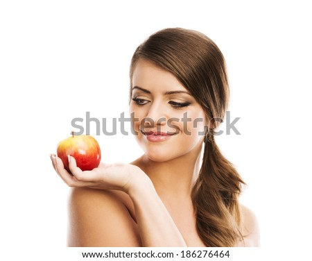 Smiling beautiful woman holding red apple while isolated on white